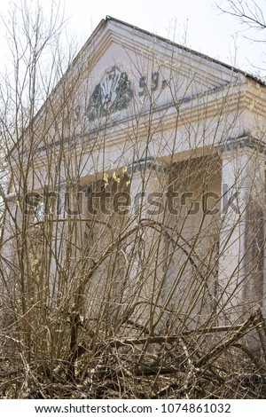 Vertical view of exterior of abandoned building built in 1959 that is now surrounded by overgrown trees and bushes.