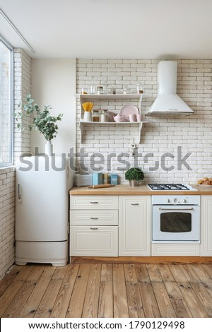 Vertical view of fridge, gas stove appliance, cooking hood, built in oven equipment, kitchenware supplies on shelves and green plants in kitchen at modern house with white interior design