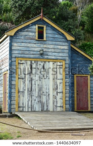 Vertical view of historic wooden boat shed with paint peeling off weathered walls. #1440634097
