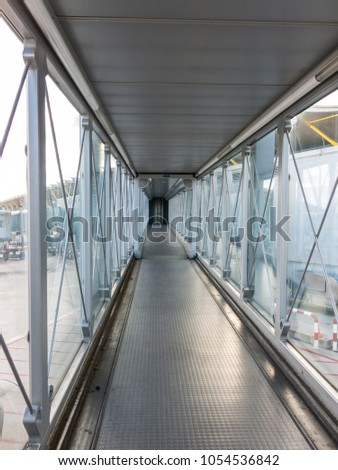 Vertical view of the airport bridge, where passengers connect with the plane. #1054536842