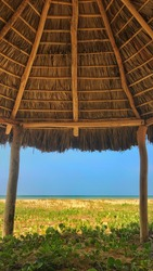 Vertical view of the beach and the sea through a hut made of wooden logs and palms