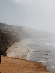 Vertical viewpoint looking out on an empty, misty, sandy, beach in San Diego, California
