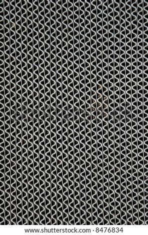 Vertical wavy silver lines of a metal grate on a pathway.