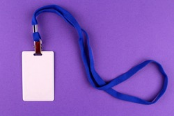 Vertical white badge with a blue lace around the neck. Badge on a purple background