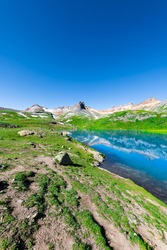 Vertical wide angle view of turquoise Ice lake near Silverton, Colorado on summit rocky mountain peak and snow in August 2019 summer