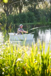 Vertical wide shot of an elderly man fishing in a rowboat over a lake with tall grass blades in the foreground.