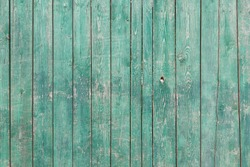 Vertical wooden boards. Old abstract grunge background with wooden fence with traces of crack, scratches, damage, fractures, peeling green paint.