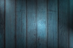 Vertical wooden planks with peeling blue paint, creative lighting and copy space. Abstract trendy wooden natural texture background