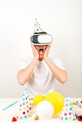 Verticled frame - a man wearing 3d glasses sitting in front of a deck full of holiday stuff and shows strong expressions while in a virtual reality