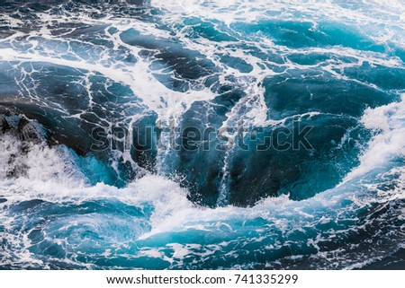 vertiginous, swirling foamy water waves at the ocean photographed from above #741335299