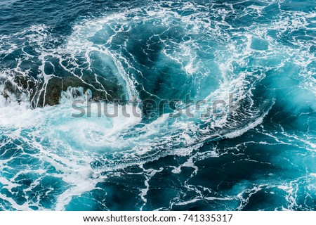 vertiginous, swirling foamy water waves at the ocean photographed from above #741335317