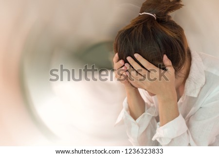 Vertigo illness concept. Asia Woman hands on his head felling headache dizzy sense of spinning dizziness with motion blurred background