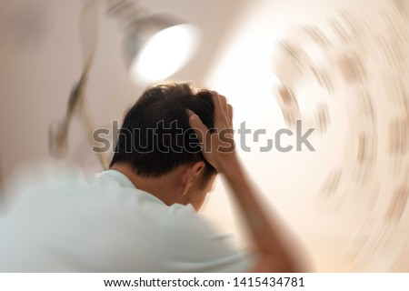Vertigo illness concept. Man hands on his head felling headache dizzy sense of spinning dizziness,a problem with the inner ear, brain, or sensory nerve pathway.