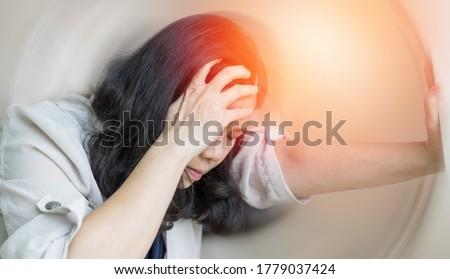 Vertigo illness concept. Woman hands on his head felling headache dizzy sense of spinning dizziness,a problem with the inner ear, brain, or sensory nerve pathway.
