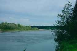 Vertluga river was photographed in Nizhny Novgorod region of Russia. Impenetrable taiga is located around wide river. Huge river is navigable. Sandy shore is visible in background.