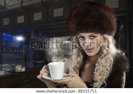 very attractive blond curly woman in elegant dress with fur stole and hat drinking a cup of tea