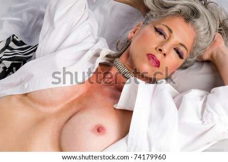 Very Attractive Woman At Her Fifities Laying Nude In Bed Stock