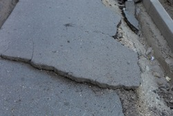 Very bad urban environment with ruined and broken asphalt on the sidewalk. Background