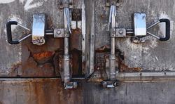 Very badly rusted truck door. Truck lock with protective seals. Container door. Security of cargo shipment. Rusted metal doors background.