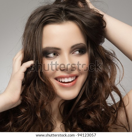 Very beautiful and happy woman hands in her hair pulling.
