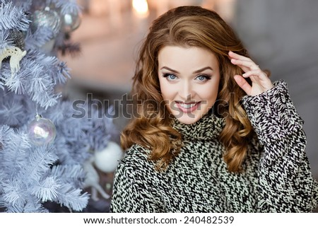 Very beautiful and sensual blonde girl in a knitted sweater smiles on the background of the Christmas tree, close up