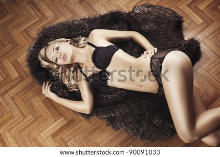 very beautiful blond and sexy young woman in underwear laying down on floor and covering with fur, she looks in to the lens with actractive eyes and touch left hip with left hand.