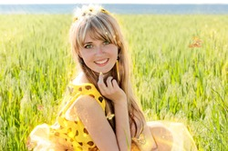 Very beautiful blue-eyed, blond girl with long hair as a sunny princess. With a glowing crown on his head and radiating a warm light, yellow magical butterflies fly to her. The sun, a sunny bright day