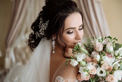Very beautiful, dark-haired bride with ornaments in her hair, with earrings with precious stones and lush white lace dress on your wedding day  Girl paints lips and sprays perfume