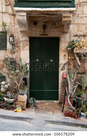 Very beautiful door, surronded by plants and flowers.
