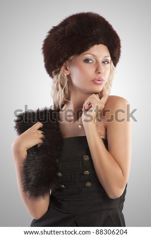 very beautiful fashion woman wearing an elegant black dress with boot and winter fur hat with stole on grey spotlight background