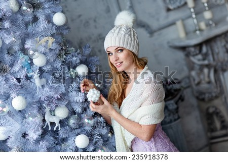 Very beautiful girl with blue eyes in a white hat costs about silver Christmas tree