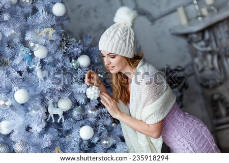 Very beautiful girl with blue eyes in a white hat costs about silver Christmas tree and looks at the ball
