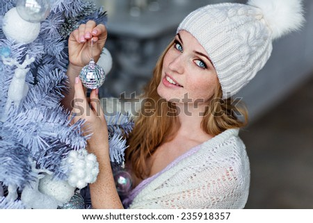 Very beautiful girl with blue eyes in a white hat costs about silver Christmas tree and smiling, close up