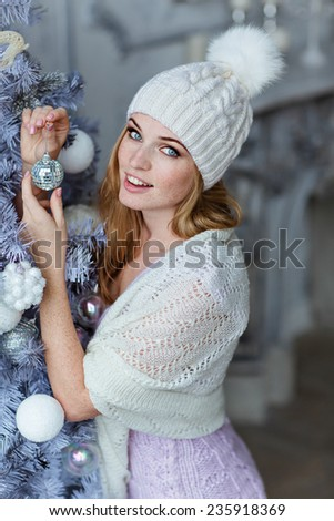 Very beautiful girl with blue eyes in a white hat costs about silver Christmas tree and smiling