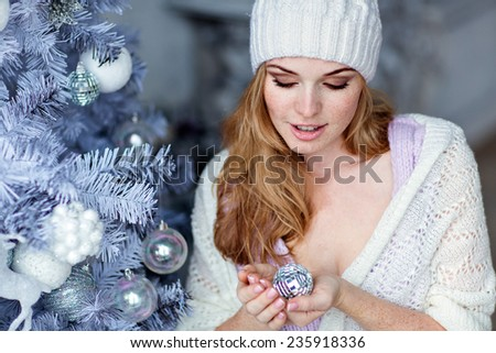 Very beautiful red-haired girl with blue eyes in a white hat about silver Christmas tree and looks at the ball