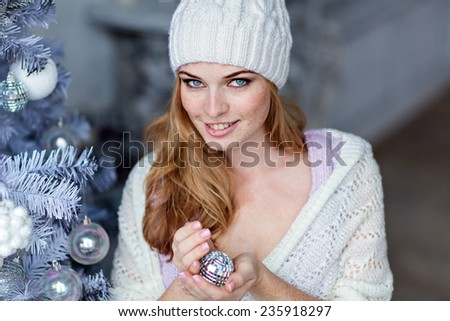 Very beautiful red-haired girl with blue eyes in a white hat about silver Christmas tree and smiling