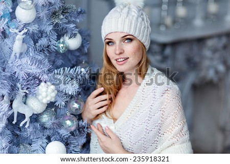 Very beautiful red-haired girl with blue eyes in a white hat about silver Christmas tree on a grey background