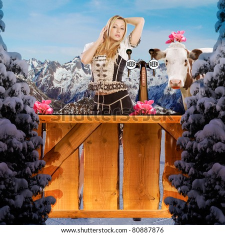 very beautiful tiroler ski girl in the snow behind a wooden bar