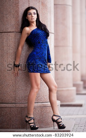 very beautiful young brunette woman wearing a blue mini dress in the street