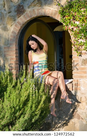 Very beautiful young woman posing in the window of old medieval house in the light of bright sun at early morning