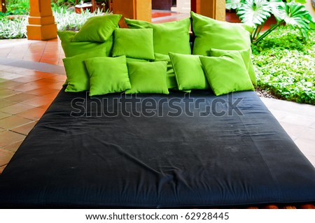 Very big bed with many green pillows