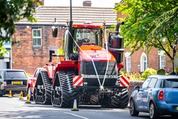 Very big red combine tractor with rubber tracks and massive exhaust as unique individual wedding car with ribbons parked on residential street outside church in village in summer sunshine