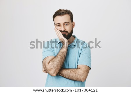 Very bored adult man with beard holding hand on cheek while support it with another crossed hand, looking tired and sick, over gray background. Father attends parents day at school