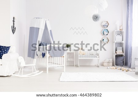 Very bright and pure baby room decor in marine style, with canopy cot, white cradle and carpet #464389802