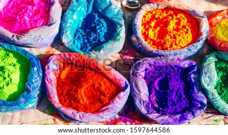 very bright multicolored paint powders in bags and a small spoon. paints for the holiday of Holi