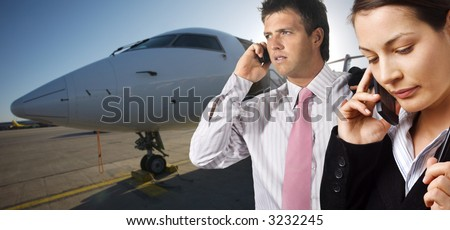 Very busy young businesspeople talk on mobiles. They are on the runaway in front of a corporate jet.
