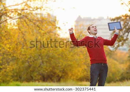 Very cheerful man celebrating victory. Young man using tablet computer on autumn street and city park.  Student using tablet computer. Man winner. Man celebrating, arms raised, expressing positivity.
