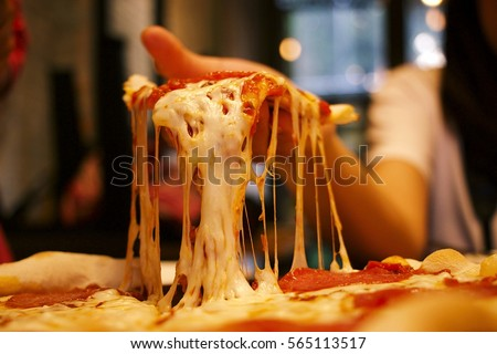 Very cheesy pizza slice in hand