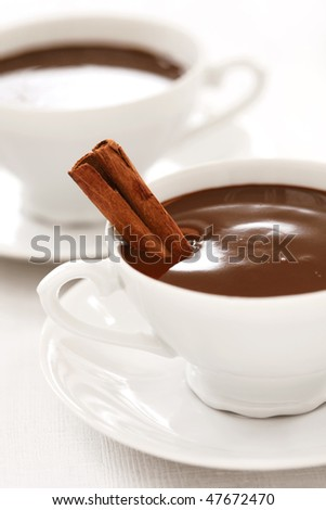 very chocolaty hot chocolate in white cups with cinnamon stick