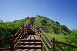 very clean and modern outdoor wooden stair on uphill in forest in South Korea, Busan, Nam-gu, Yongho-dong, Oryukdo Island, perfect for hiking and taking a walk, one of favorite place in Korea spring